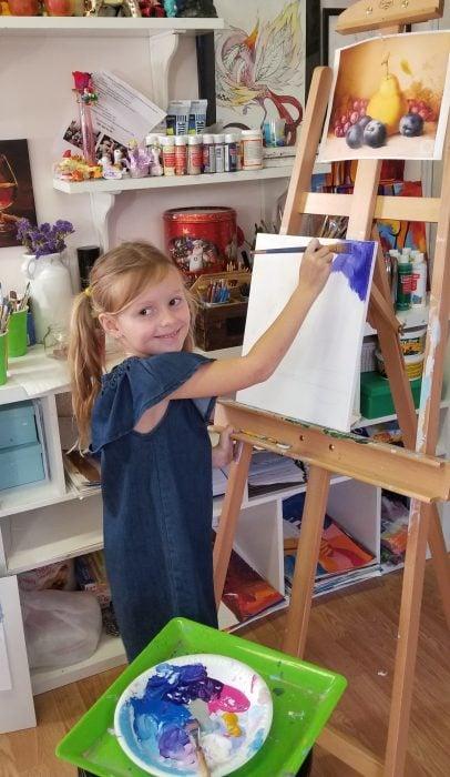 ребенок рисует на холсте